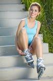 kvinna som sätter på gående rollerblading för skridskor Royaltyfri Fotografi