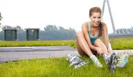 kvinna som sätter på gående rollerblading för skridskor Royaltyfria Bilder