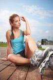 Kvinna som sätter på gående rollerblading för skridskor Arkivbilder