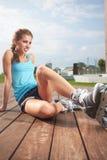 Kvinna som sätter på gående rollerblading för skridskor Royaltyfri Foto
