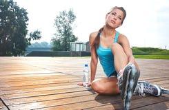 Kvinna som sätter på gående rollerblading för skridskor Royaltyfri Bild