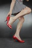 Kvinna som sätter på röda skor över grå färger fotografering för bildbyråer
