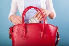 Kvinna som sätter preventivpillerar till den röda läderhandväskan Royaltyfri Fotografi
