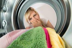 Kvinna som sätter in stinka kläder i tvagningmaskin fotografering för bildbyråer