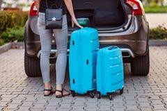 Kvinna som sätter två blåa plast- resväskor till bilstammen arkivfoton