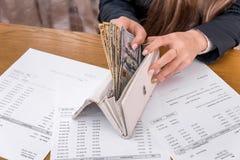 Kvinna som söker efter pengar i plånboken, köpbeställning royaltyfri bild
