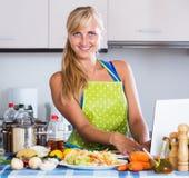 Kvinna som söker recept i internet Arkivfoton