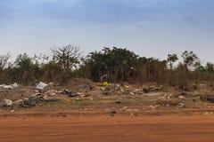 Kvinna som samlar avskräde i en nedgrävning av sopor i utkanten av staden av Bissau, i Guinea-Bissau, Västafrika royaltyfri bild
