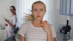 Kvinna som ser äpplet på den tand- kliniken stock video