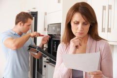 Kvinna som ser angången på den Bill For Repair Of Kitchen anordningen royaltyfri foto