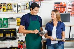 Kvinna som ser arbetaren som nallar kreditkorten Arkivbild