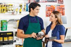 Kvinna som ser arbetaren som nallar kreditkorten Royaltyfri Foto