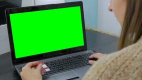 Kvinna som ser bärbara datorn med den gröna skärmen Royaltyfri Bild