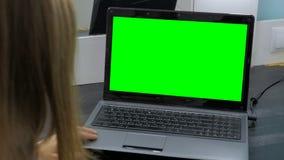 Kvinna som ser bärbara datorn med den gröna skärmen Arkivfoton