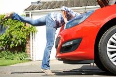 Kvinna som ser bilmotorn med huvudet som försvinner under huven Royaltyfri Foto