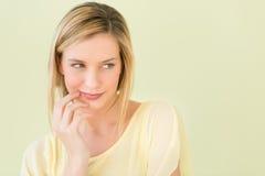 Kvinna som ser bort mot grön bakgrund Fotografering för Bildbyråer