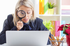 Kvinna som ser datorskärmen till och med ett förstoringsglas Royaltyfri Foto