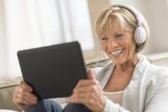 Kvinna som ser den Digital minnestavlan, medan genom att använda hörlurar Royaltyfria Bilder