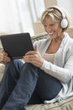 Kvinna som ser den Digital minnestavlan, medan genom att använda hörlurar arkivfoto