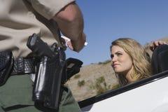 Kvinna som ser den mogna trafiktjänstemannen Arkivfoto