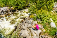 Kvinna som ser det snabba flödande vattnet av Joffre Creek Arkivbild