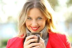 Kvinna som ser dig som rymmer en kopp kaffe i vinter Fotografering för Bildbyråer