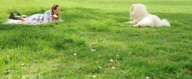 Kvinna som ser en hund för käkkäk på ängen Royaltyfri Fotografi