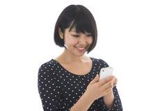 Kvinna som ser en smartphone Fotografering för Bildbyråer