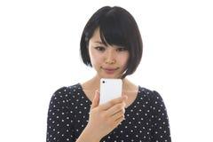 Kvinna som ser en smartphone Arkivfoto