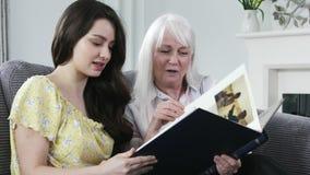 Kvinna som ser fotoalbumet med den vuxna sondottern stock video