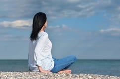Kvinna som ser havet mot arkivfoto