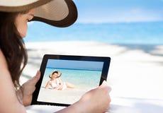 Kvinna som ser hennes bild på den digitala minnestavlan på stranden Royaltyfri Fotografi