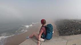 Kvinna som ser horisonten med havet i Portugal Tom strand i Povoa de Varzim, Portugal på dimmig höstdag arkivfilmer