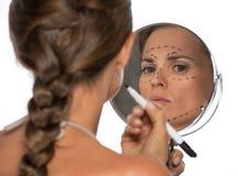 Kvinna som ser i spegel- och plastikkirurgifläckar Royaltyfri Bild