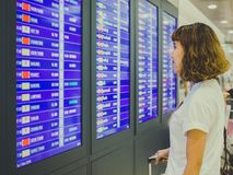Kvinna som ser informationsbrädet i uttryck för internationell flygplats arkivfoton