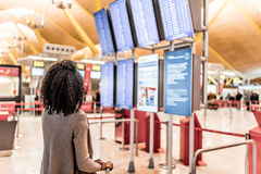 Kvinna som ser informationspanelen om schema i flygplatsen arkivbilder