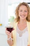 Kvinna som ser kameran med henne drink av wine 库存图片
