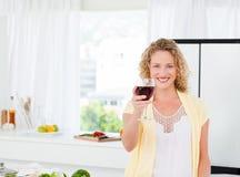 Kvinna som ser kameran med henne drink av wine 免版税库存照片