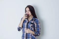 Kvinna som ser kameran och dricker rött vin Arkivfoto