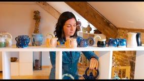 Kvinna som ser lergodskrukan arkivfilmer
