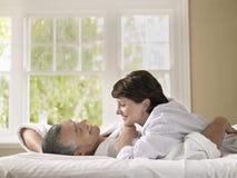 Kvinna som ser maken, medan ligga i säng royaltyfria foton