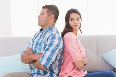 Kvinna som ser mannen, medan sitta på soffan Royaltyfri Fotografi