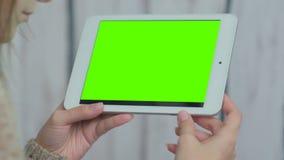Kvinna som ser minnestavladatoren med den gröna skärmen Royaltyfria Bilder