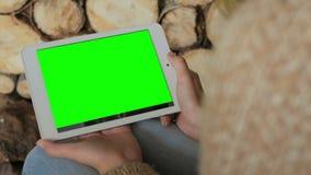 Kvinna som ser minnestavladatoren med den gröna skärmen Royaltyfri Bild