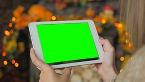Kvinna som ser minnestavladatoren med den gröna skärmen Royaltyfri Fotografi
