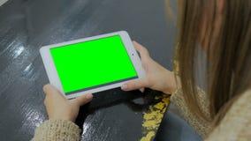 Kvinna som ser minnestavladatoren med den gröna skärmen Arkivbild