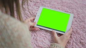 Kvinna som ser minnestavladatoren med den gröna skärmen Arkivfoto