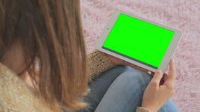 Kvinna som ser minnestavladatoren med den gröna skärmen Arkivfoton