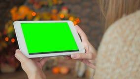 Kvinna som ser minnestavladatoren med den gröna skärmen Royaltyfri Foto