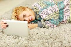 Kvinna som ser minnestavladatoren, medan ligga på mattan Arkivbild